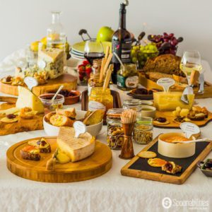 Wine and Cheese Tasting Party with Apricot Fruit Spread, Old Fashionable Fig Preserve, Apple Caramelized Onion Spread, Black Olive Tapenade and Strawberry Chipotle Jam. Cheese and jam pairing in beautiful rustic wooden boards. Spoonabilities.com