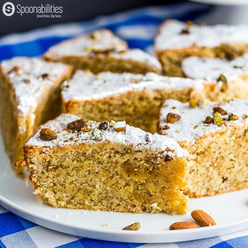 Six slices of Persian Almond Cardamom Pistachio Cake on a round white plate. This cake moist and aromatic dessert recipe. Served for Passover using Kosher ingredients. Featuring Pure Cottonseed oil from Acala Farms. Available at Spoonabilities.com