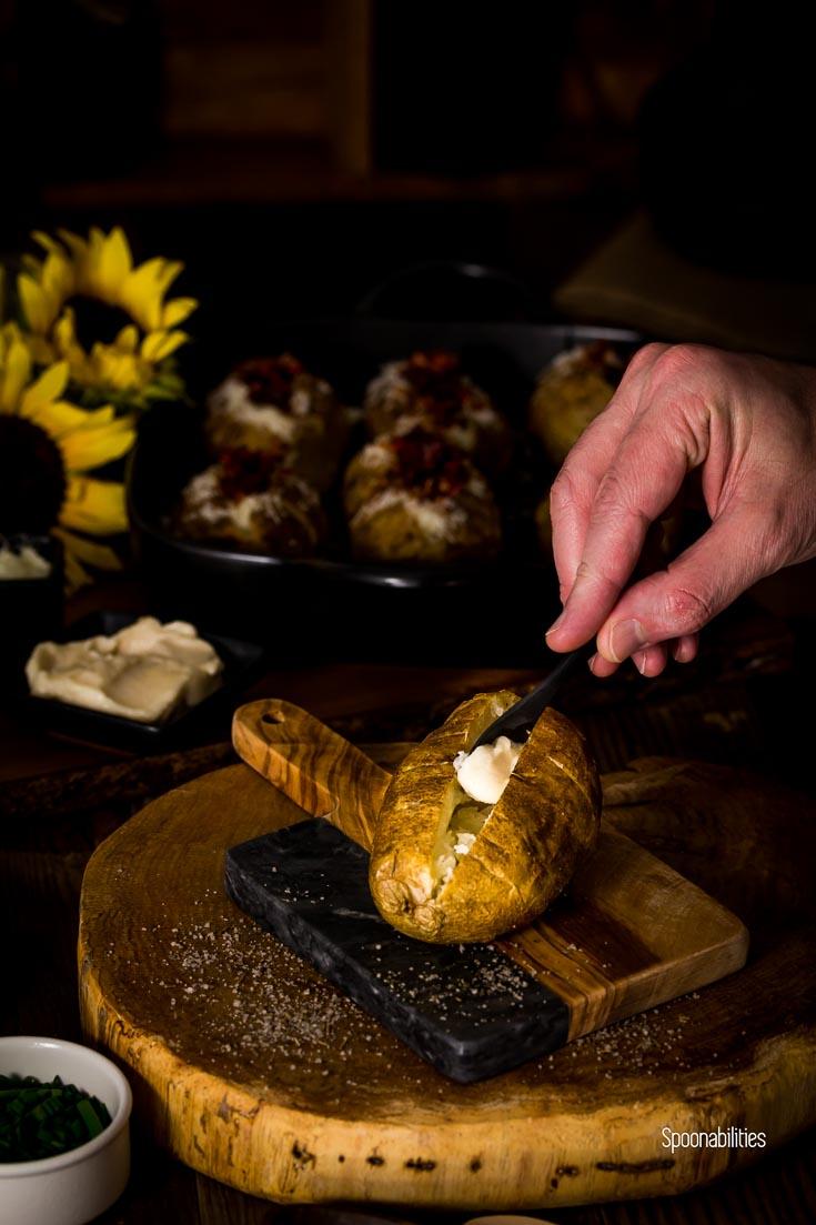 Adding a TableSpoon of aioli to the baked Spanish style baked potato, on a rustic cutting board. Spoonabilities.com
