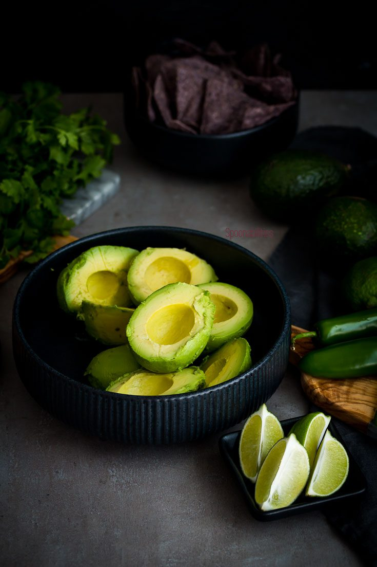 The best guacamole recipe is easy to make. In this photo the avocado meat is in a round black bowl with lime wedges, jalapeño and cilantro. Spoonabilities.com