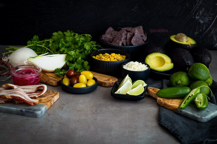 The best guacamole recipe with corn, bacon, cotija Cheese, lime, cilantro, jalapeño, coriander, cumin & salt. Spoonabilities.com