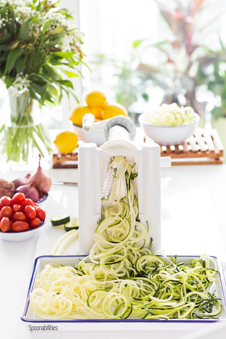Making Zucchini noodles with the Paderno Spiralizer. Noodles in a white tray with tomatoes, shallots & lemons in the background