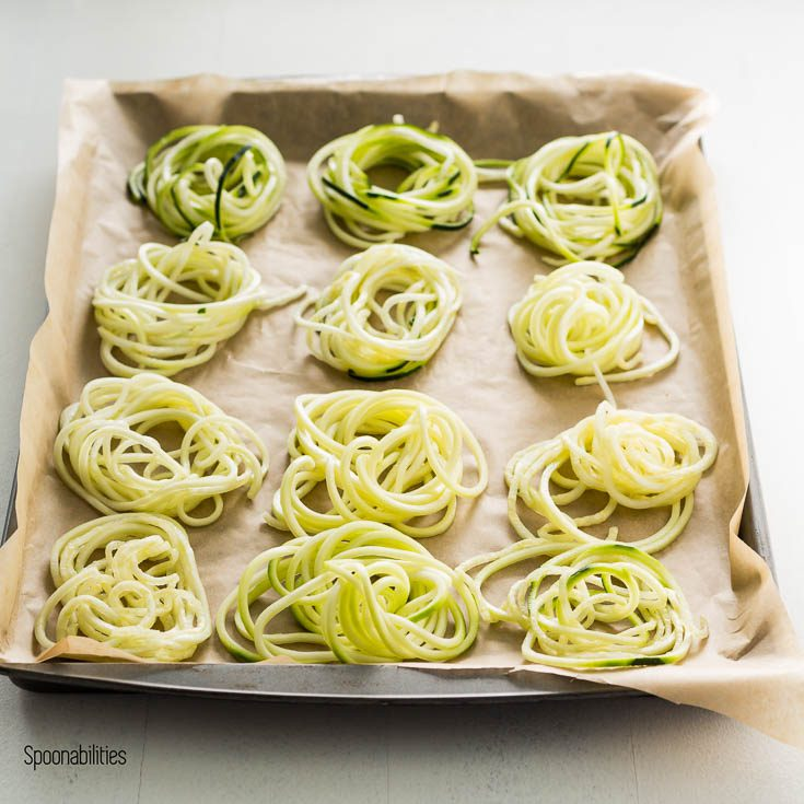 Baking tray with 12 bird nest Zucchini noodles.This recipe inspired by Mediterranean flavors of lemon artichoke pesto. Spoonabilities.com