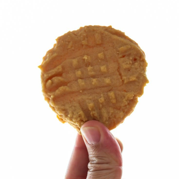 Best Peanut Butter Cookie Recipe - holding up 1 cookie. Spoonabilities