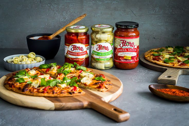 Cauliflower Crust Pizza on a wooden board with flora Fine Foods products in the back. The products are pizza sauce , baby artichokes & roasted red pepper. Spoonabilities.com