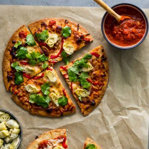 Cauliflower Crust Pizza recipe with Artichokes and Roasted Red Pepper from Flora Fine Foods. Presented with a bowl with pizza sauce and baby artichokes. Spoonabilities.com